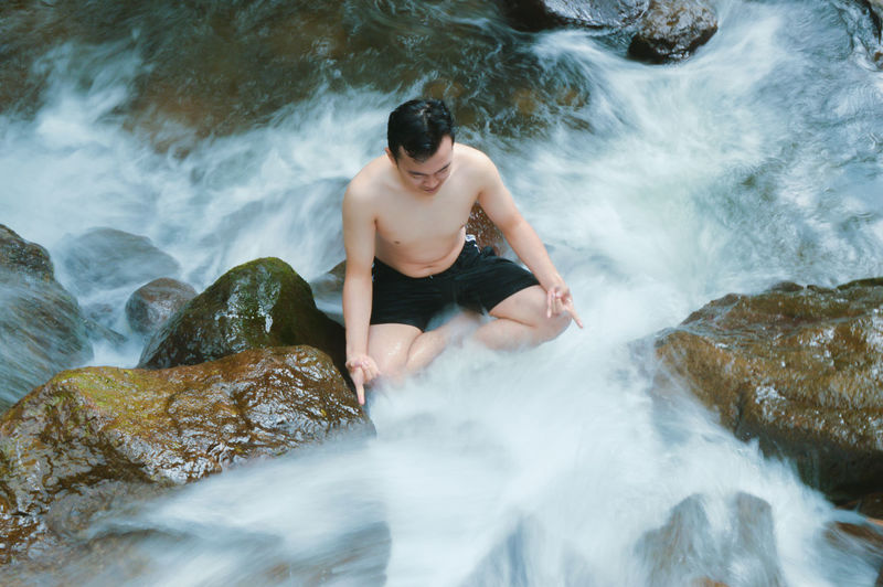 High angle view of man meditating in waterfall