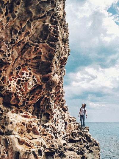Woman standing on rock formation by sea against sky