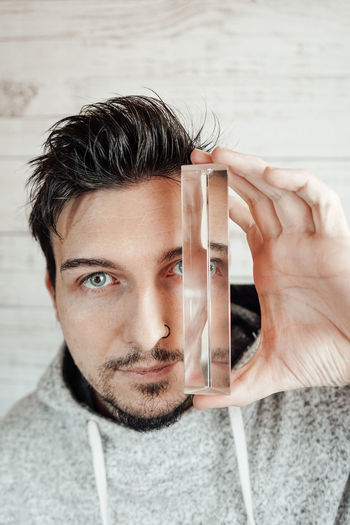 Mid adult man holding prism