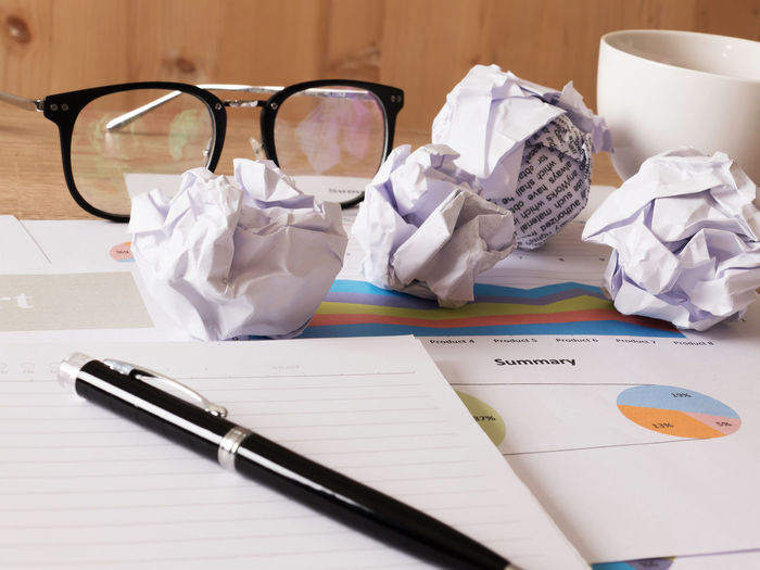 High angle view of pen with crumpled papers and financial reports on desk in office