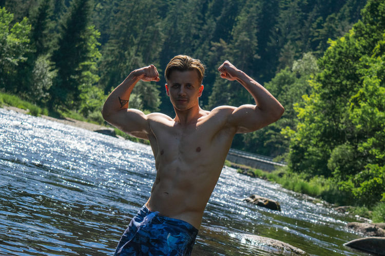 Portrait of shirtless man flexing muscles while standing by river in forest