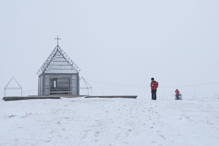 Rear view of people on snow covered against sky