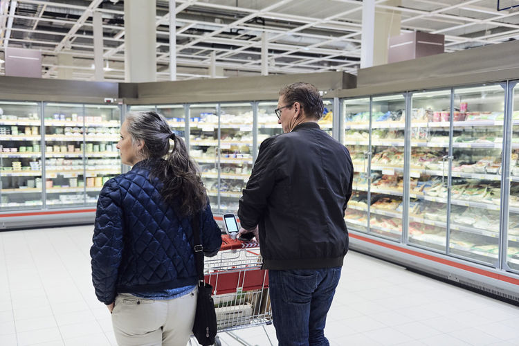 Rear view of couple standing in store