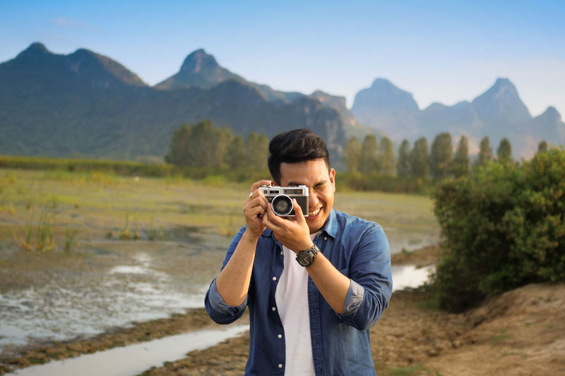 Technology Photography Themes Real People One Person Mountain Standing Photographing Scenics - Nature Leisure Activity Camera - Photographic Equipment Nature Men Activity Lifestyles Waist Up Casual Clothing Beauty In Nature Holding Mountain Range Front View Outdoors Digital Camera Photographer
