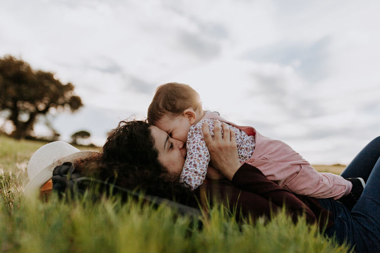 Mother kissing daughter while lying on lawn against sky