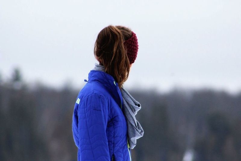 Side view of woman standing against sky during winter