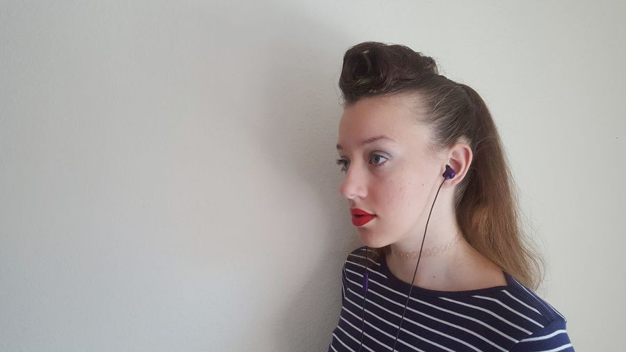 Close-Up Of Thoughtful Teenage Girl Standing Against Wall