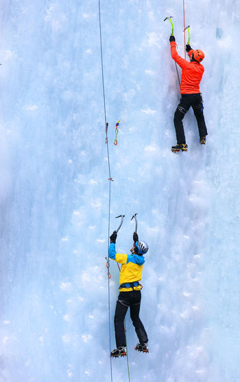 Rear view of people ice climbing