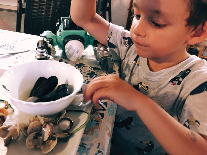 Close-Up Of Boy Looking At Seafood In Bowl On Table