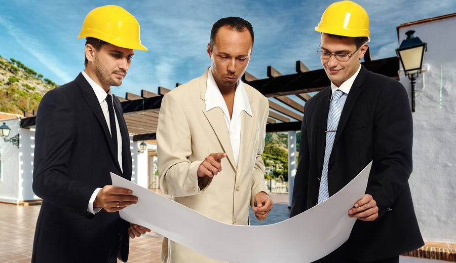 Construction team at business meeting. Studio shot ARCHITECT Business Meeting Construction Man Meeting Plan Suit Work Worker Blueprints Builder Caucasian Confident  Construction Industry Construction Work Construction Worker Engineer Engineering Foreman Group Of People Hardhat  Paper People Project Young Adult