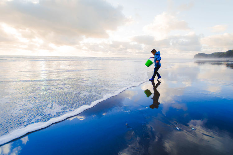 Side view of boy with bucket walking on shore at beach against sky