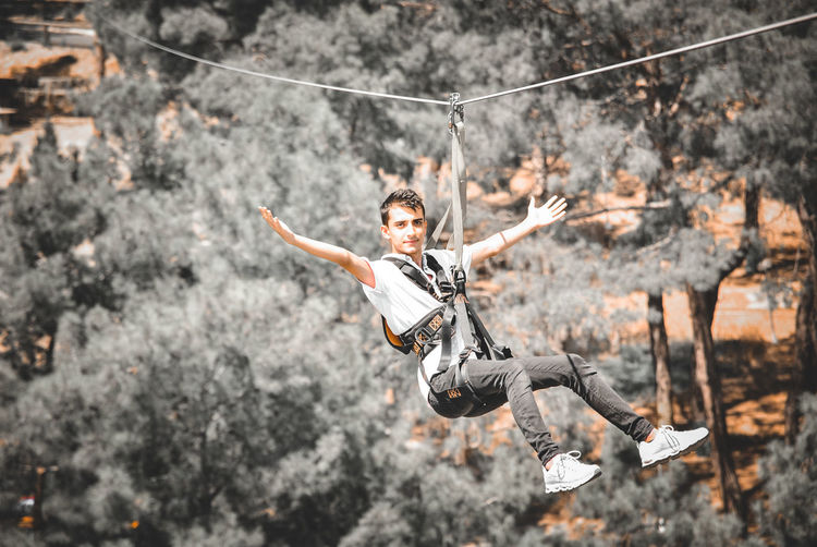 Low angle view of man hanging on rope