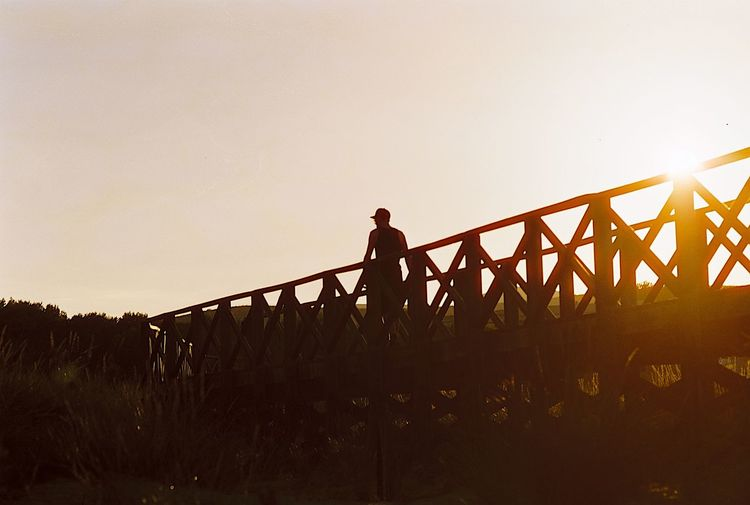 Low angle view of silhouette man standing on bridge against clear sky
