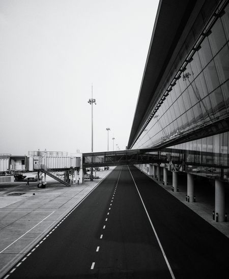 Empty road at airport against clear sky