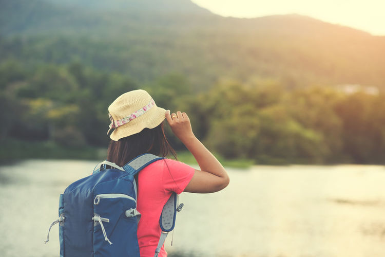 Traveler Asian woman with backpacks still looking at the beautiful of landscape happily. vintage color effect Travel Trip Adventure Backpack Backpacker Beauty In Nature Day Lake Leisure Activity Lifestyles Mountain Nature One Person Outdoors Real People Scenics Sky Standing Tree Water Women Young Adult Young Women