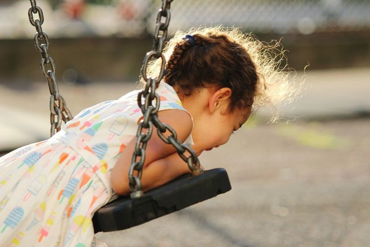Side view of girl playing with swing in playground