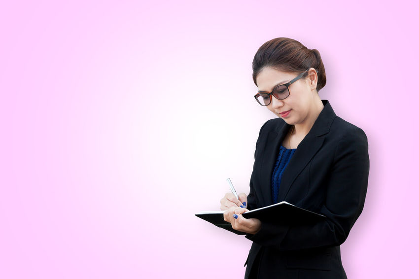 Asian businesswoman writing a note Asian  Colors Copy Space Isolated Office Reading Spectacles Thai Woman Write Backgrounds Business Businesswoman Conference Diary Eyeglasses  List Manager Notebook One Person Pen Portrait Secretary Smile Studio Shot