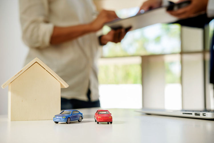 Close-up of toy cars with model home on table