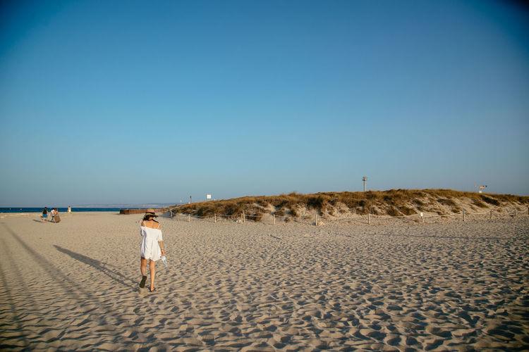 Rear view of woman walking on sandy beach