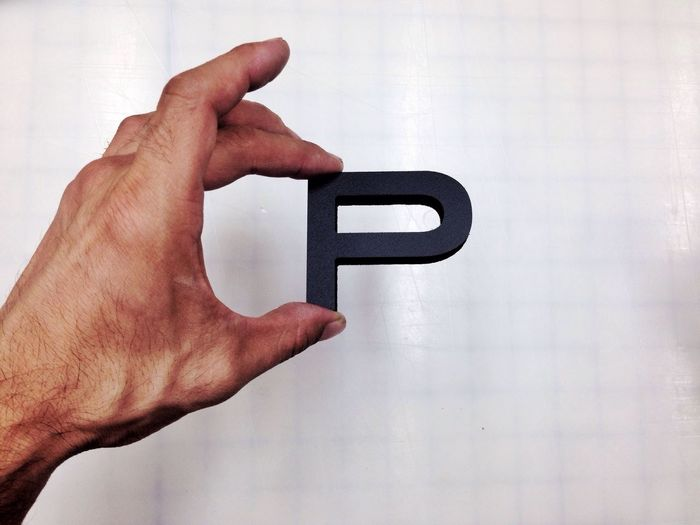 Close-up of male hand holding letter p