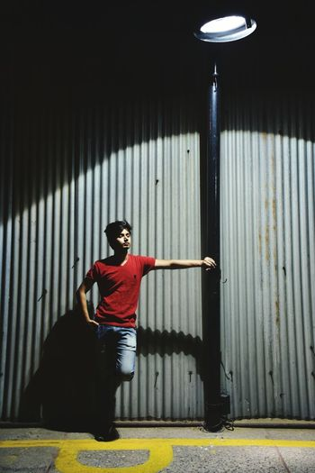 Young man leaning on street light while standing against corrugated sheet