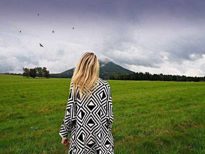 Rear view of woman standing on grassy field against sky