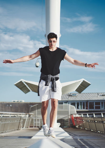 Full length of young man standing against sky