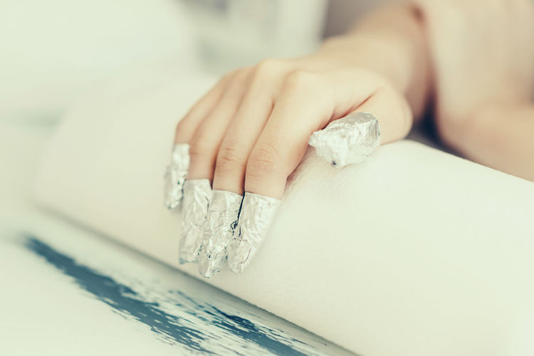 Close-up of woman fingers with wrapped in silver foil