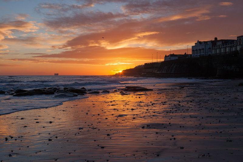 Seascape against cloudy sky at dusk