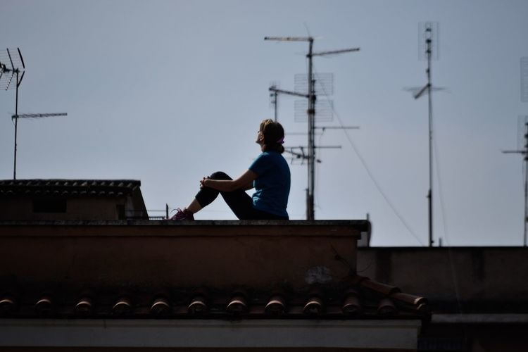 Man sitting on roof against sky
