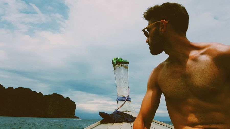 Shirtless man traveling in longtail boat on sea against sky