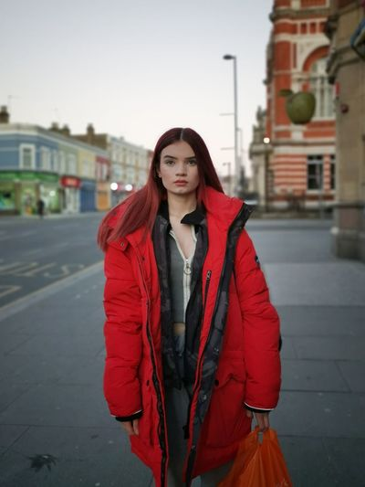 Portrait of beautiful woman standing in city