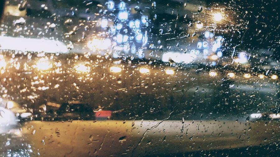 Raindrops on windshield seen through wet window