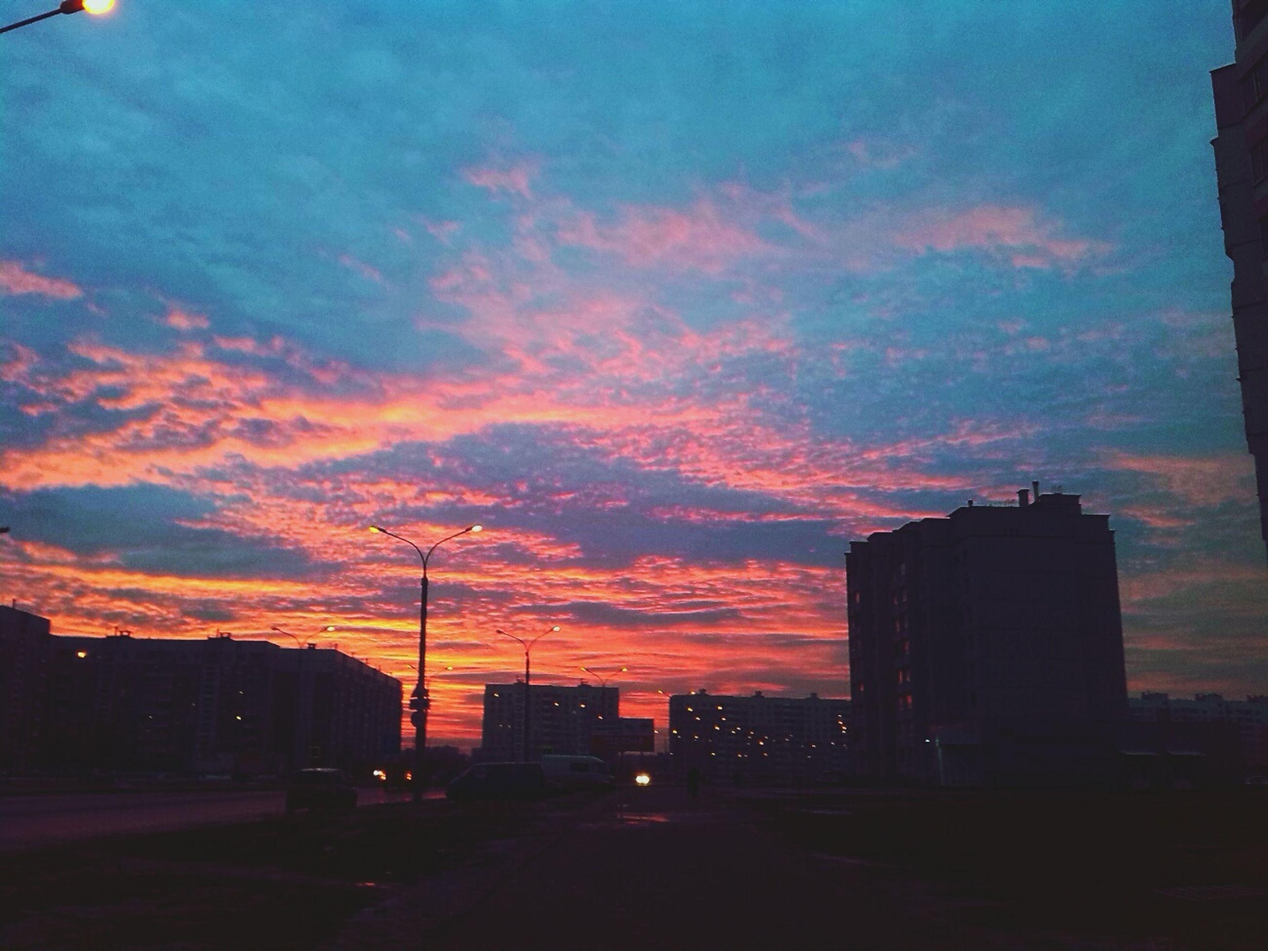 sunset, building exterior, architecture, built structure, silhouette, sky, orange color, city, cloud - sky, road, street, car, transportation, cloud, dramatic sky, dusk, street light, outdoors, building, no people