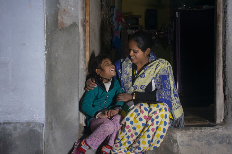 Happy indian mother and daughter sitting at outside her house