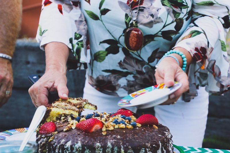 Midsection Of Woman Cutting Birthday Cake On Table