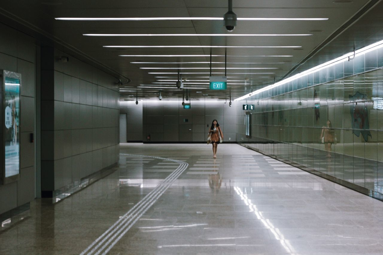 indoors, walking, one person, reflection, real people, illuminated, women, full length, architecture, standing, day, adult, people