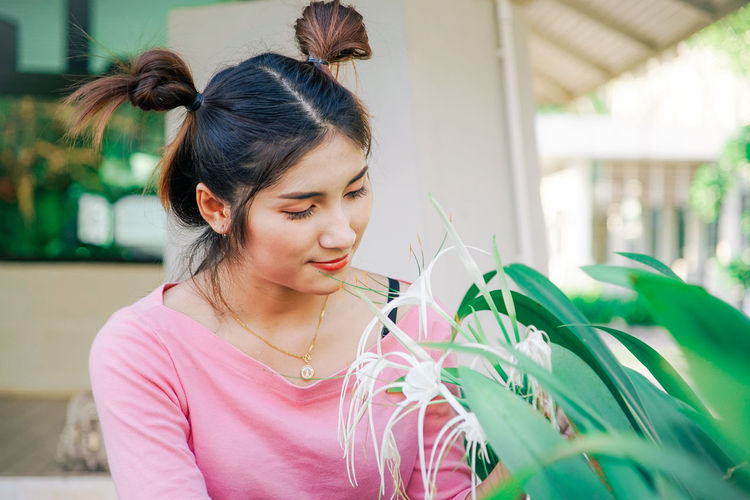Woman With Pigtails Looking At Spider Lily