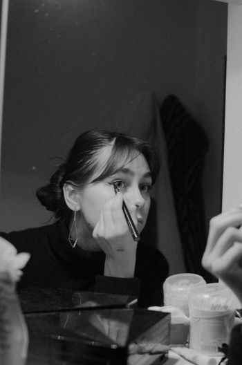 Young Woman Applying Make-Up In Front Of Mirror