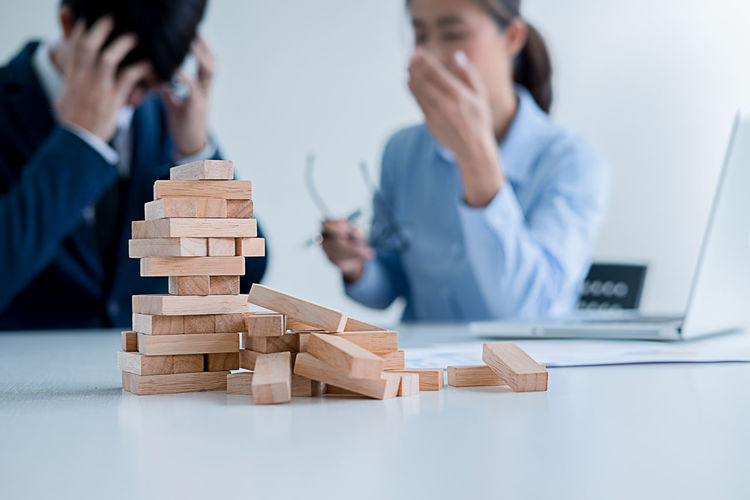 Tensed business colleagues with block removal game at desk in office