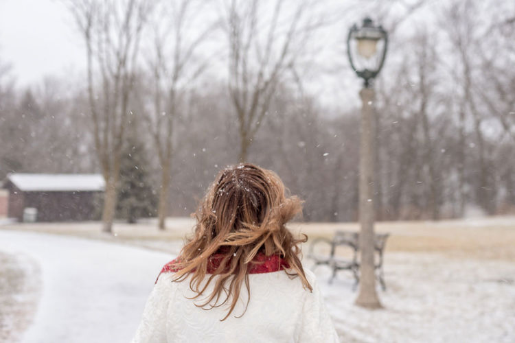 Rear view of woman standing against bare trees during snowfall