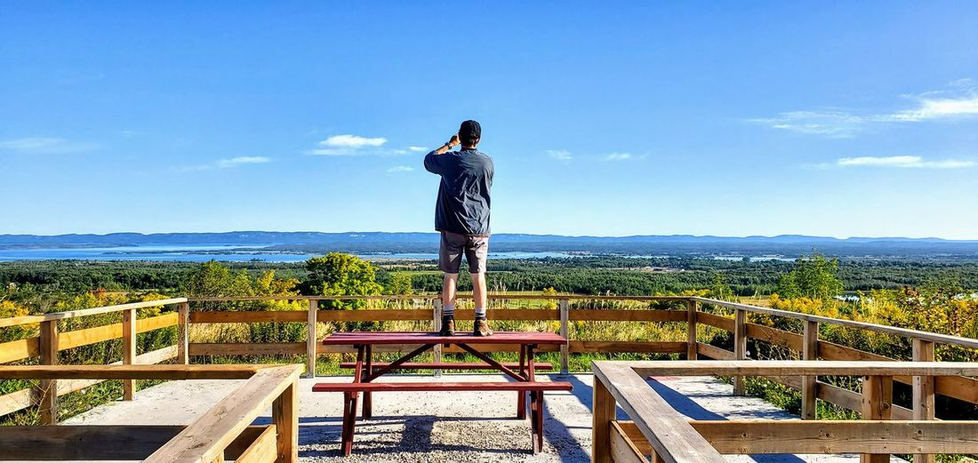 Rear view of man standing on railing against sky