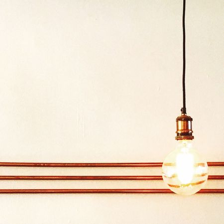 EyeEm Selects Electricity  Lighting Equipment Light Bulb Illuminated Bulb Copy Space No People Hanging Close-up Indoors  Day Interior Design Interior Copper  Pipes