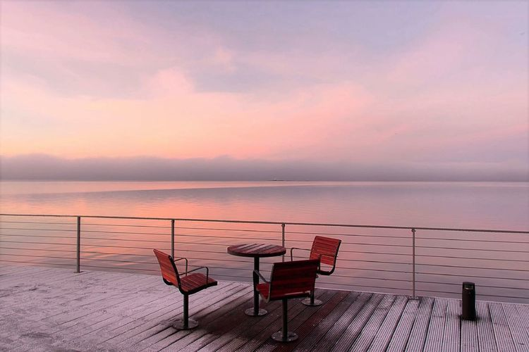 Empty chairs by sea against sky during sunset