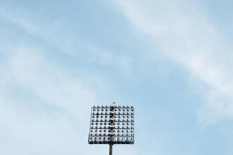 Stadium lighting mast against blue sky