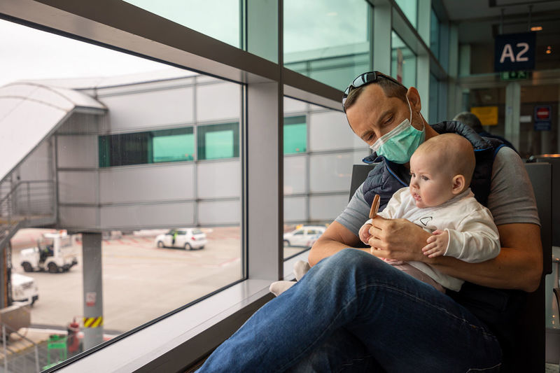 Father wearing mask sitting with daughter at airport