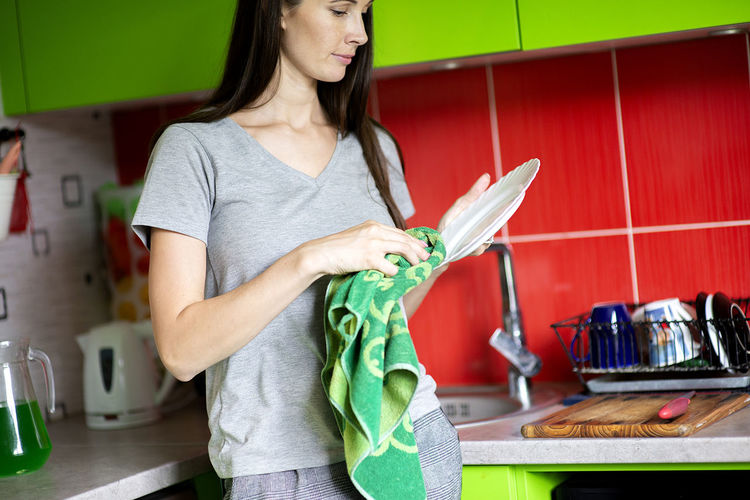 Portrait young woman in the kitchen interior wipe with dry towel clean dishes, cleaning the house.