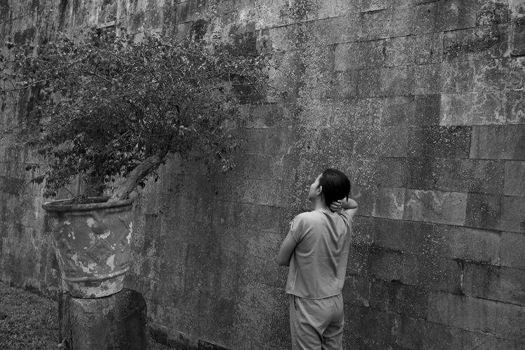 Rear view of woman looking at plant while standing by wall
