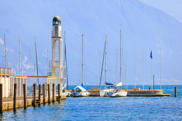 Lighthouse and boats by sea at riva del garda