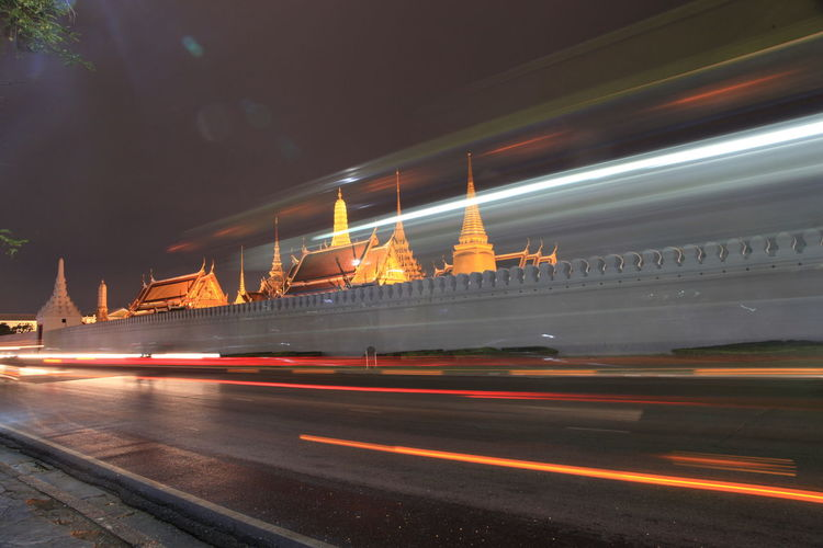 Light trails on road by buddhist temples at night